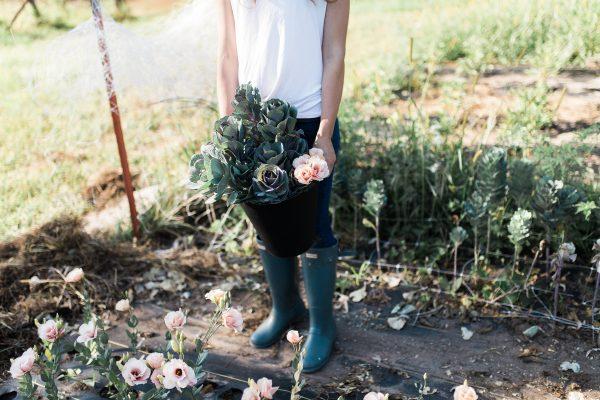 woman with bucket of flowers in field